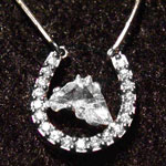 Custom necklace with a horse head cut diamond contained in a platinum horseshoe embedded with 19 smaller diamonds