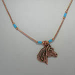 close up of horse head pendant of necklace