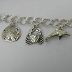 Close up of Sand Dollar and Sea Crab and Dolphin charms on Sea Life bracele