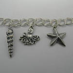 Close up of Conical Shell and Octopus and Sea Star on Nautical Charm Bracel