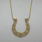 Custom 14 karat yellow gold and diamond horseshoe necklace close up